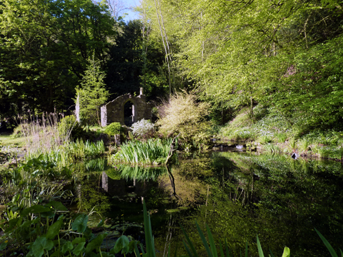 Garden folly by large natural pond and stream